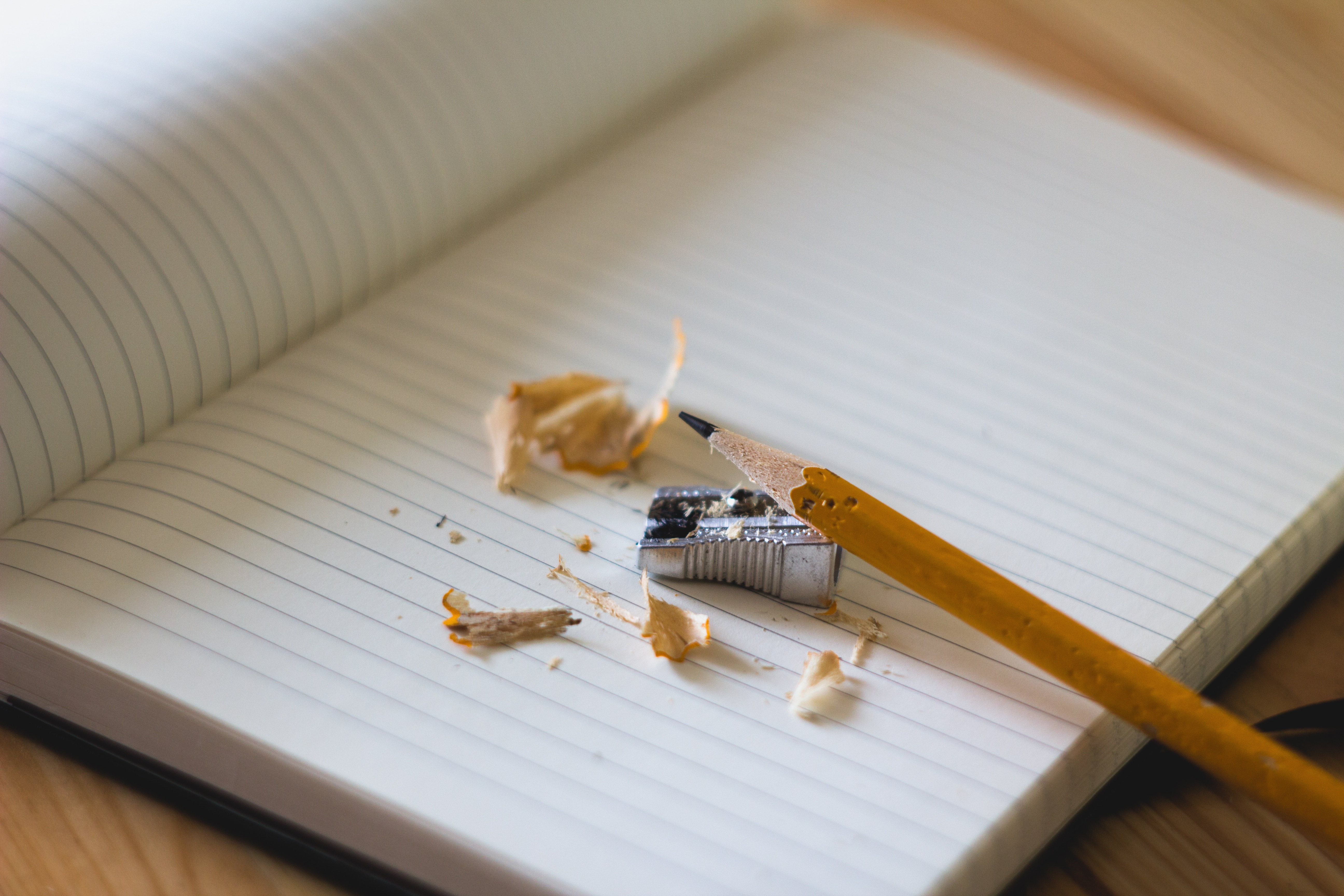 yellow pencil, pencil sharpener and fresh pencil shavings on top of a notebook