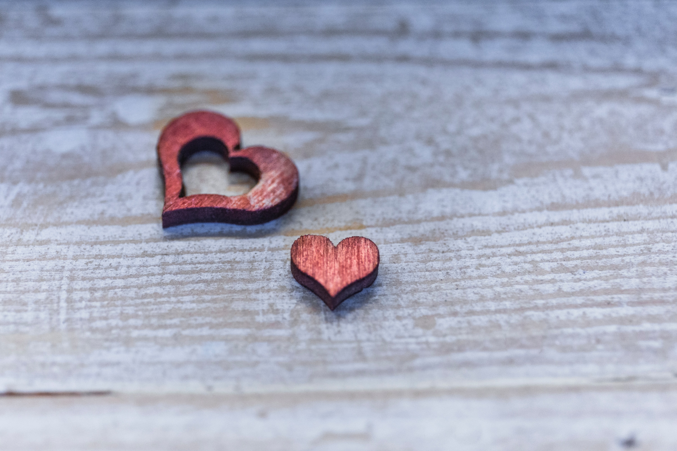 two small red wooden hearts on a gray wood plank