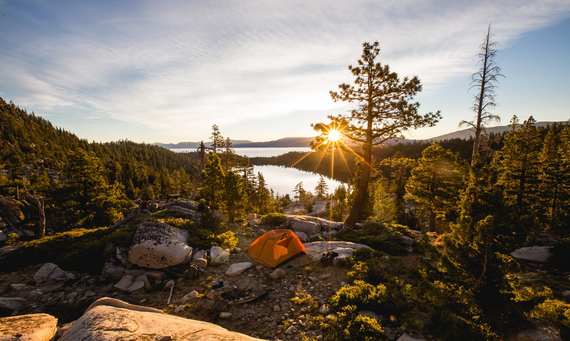 tent on a rocky outcropping overlooking the sun rising above a lake