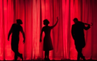 photo of silhouettes of three people on a stage with a red curtain behind them