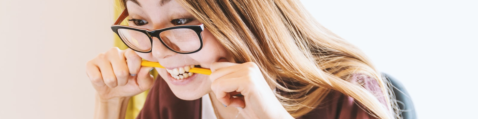 photo of a woman with glasses looking frustrated and biting on a pencil
