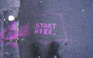 the words start here graffiti sprayed in purple on a dark gray sidewalk