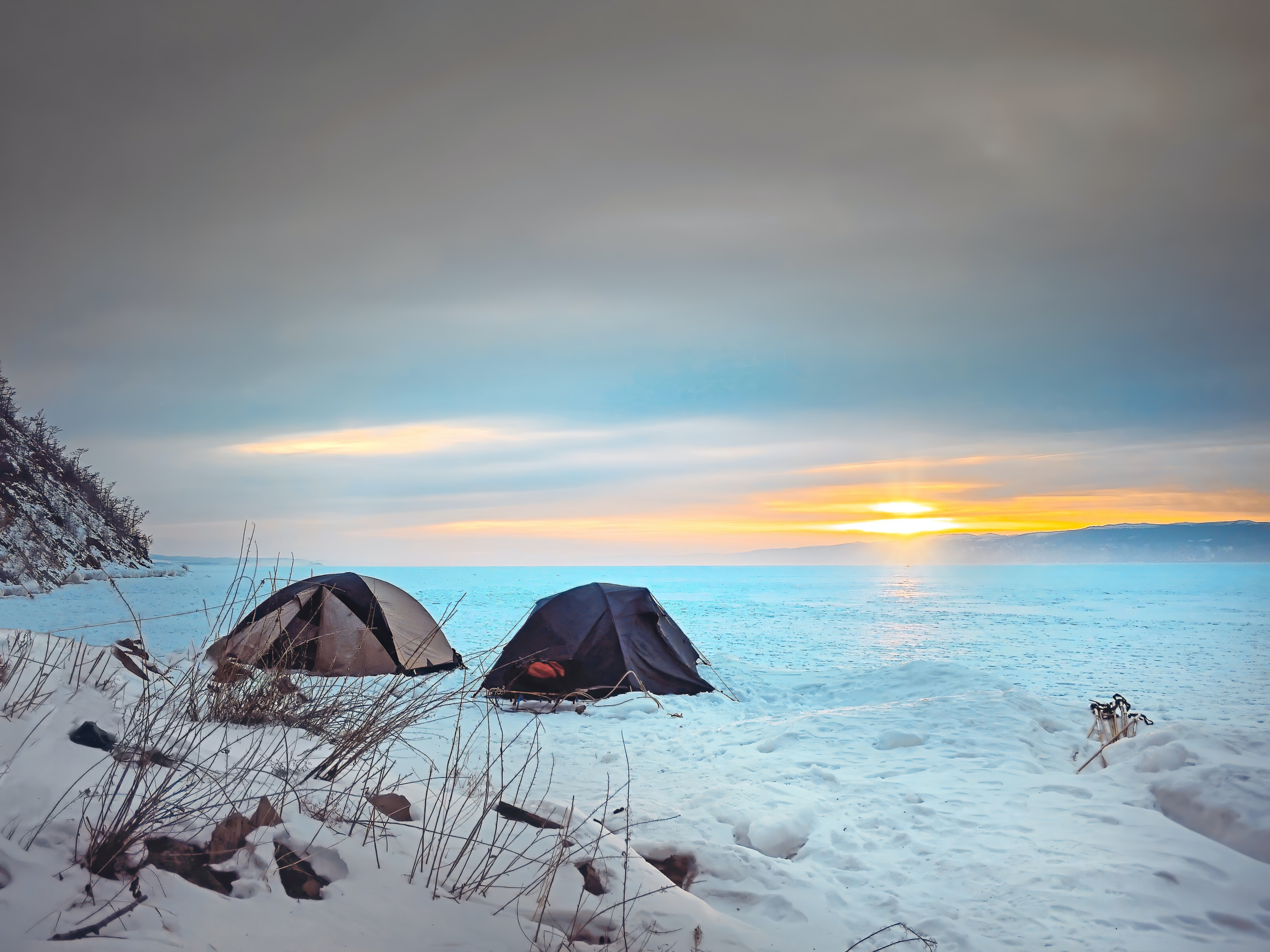 two tents on a snowy plain at sunrise