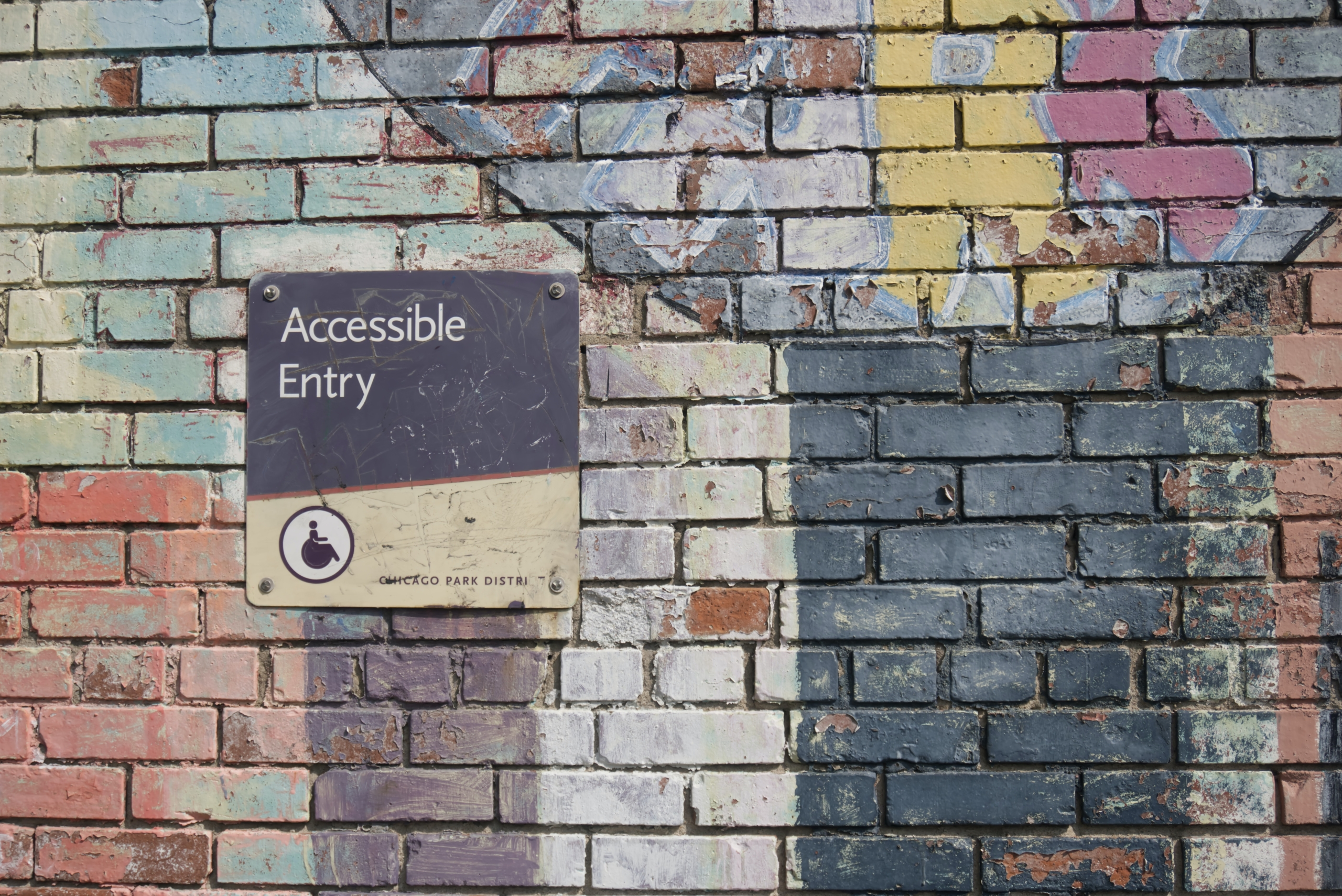 "a colorful brick way with an ""accessible entry"" sign"