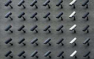 a wall covered in surveillance cameras