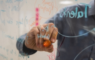 photo of a hand writing on a see-through whiteboard